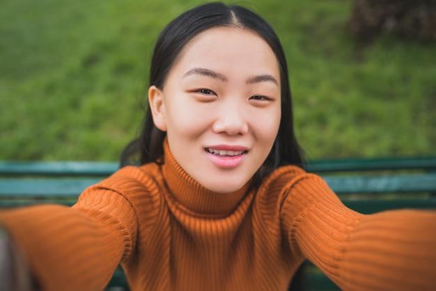 Azjatycka kobieta bierze selfie.