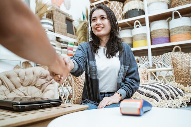 Azjatycka kobieta biznesu i klient zawierają umowę, ściskając ręce nad laptopem i elektronicznymi urządzeniami do przechwytywania danych w sklepie rzemieślniczym