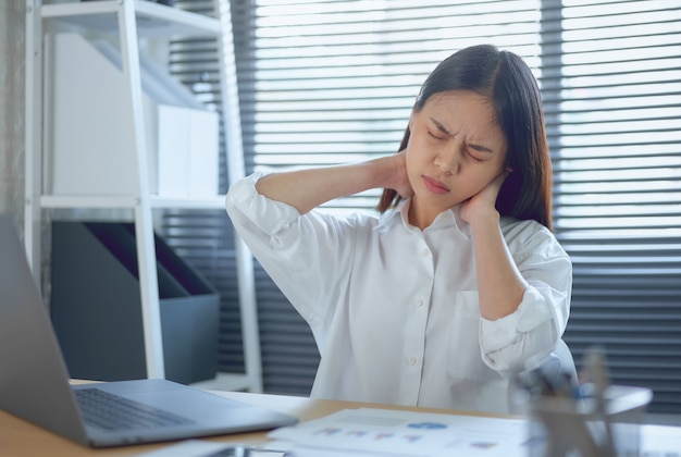Azjatycka kobieta biznesu odczuwa ból szyi, ponieważ korzysta z laptopa i pracuje przez długi czas