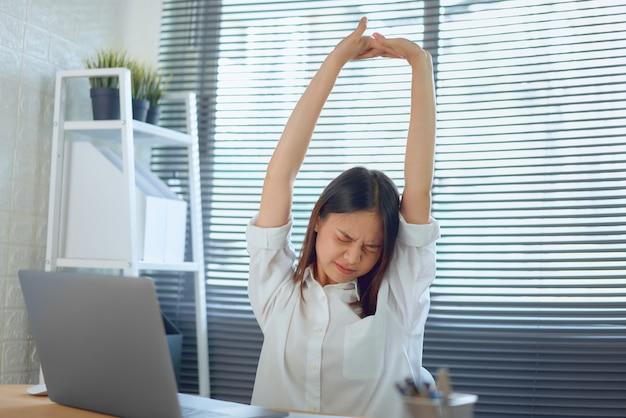 Azjatycka kobieta biznesu podnosi rękę nad głowę, aby złagodzić ból i zmęczenie po ciężkiej pracy.