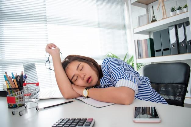 Azjatycka kobieta biznesu śpi z powodu wyczerpania ciężką pracą na biurku.