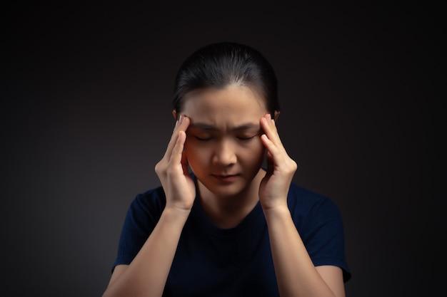 Azjatycka kobieta była chora na ból głowy, dotykając jej głowy stojącej na białym tle na tle.
