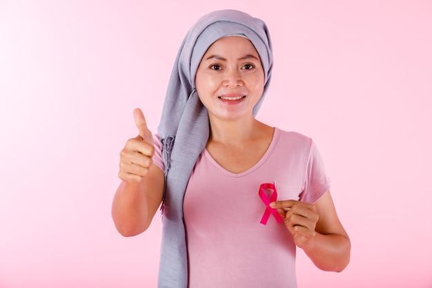 Azjatycka kobieta chora na raka sutka w swetrze trzymającym różową wstążkę i pokazująca kciuki do góry na białym tle na różowym tle pustej przestrzeni studio, opieka zdrowotna, koncepcja medycyny