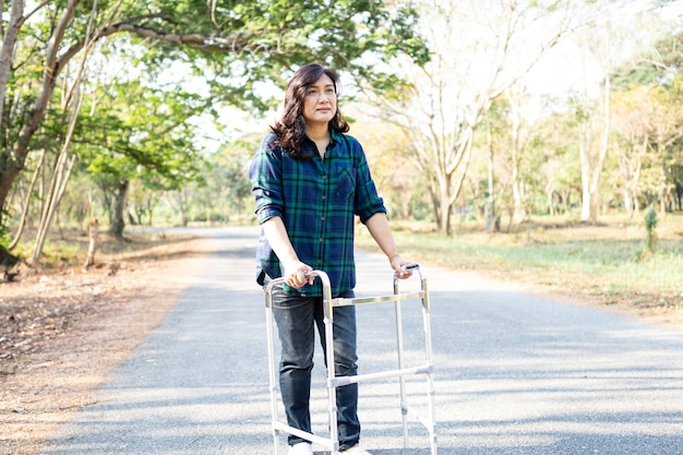 Azjatycka kobieta cierpliwa spacer z chodzikiem w parku