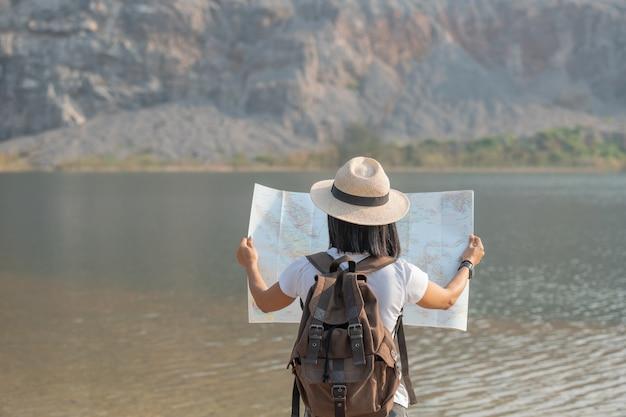 Azjatycka kobieta ciesząca się pięknem przyrody patrząca na górskie jezioro