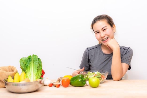 Azjatycka kobieta cieszy się jedzący sałatkowego warzywa