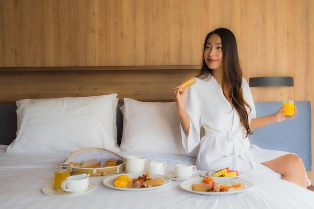 Azjatycka kobieta cieszy się z śniadaniem na łóżku