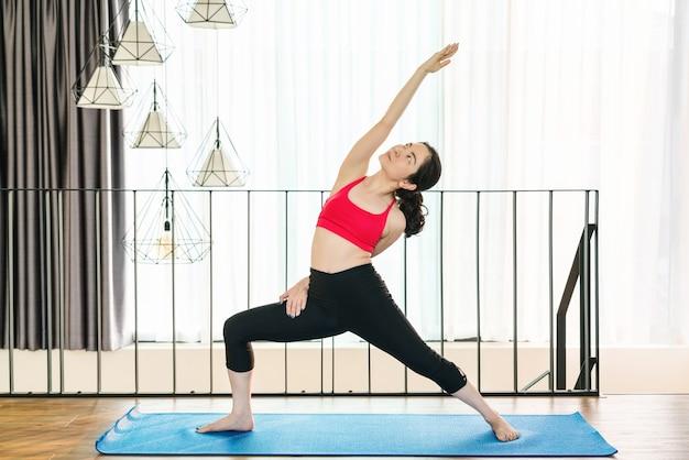 Azjatycka kobieta ćwicząca jogę w domu, gdy epidemia covid19 i blokada