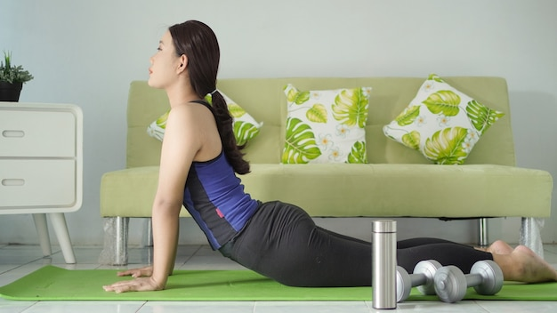 Azjatycka kobieta ćwicząca jogę w domu, rozgrzewająca elastyczność