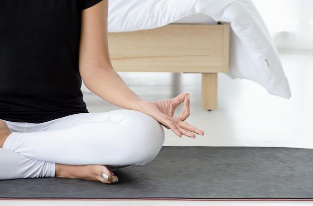 Azjatycka kobieta ćwiczy joga, robi half lotus pozie z mudra gestem na macie w sypialni