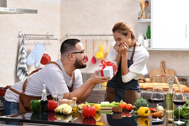 Azjatycka kobieta czuje się szczęśliwa, gdy jest zaskoczona prezentem od chłopaka podczas wspólnego gotowania w kuchni i zdrowego jedzenia