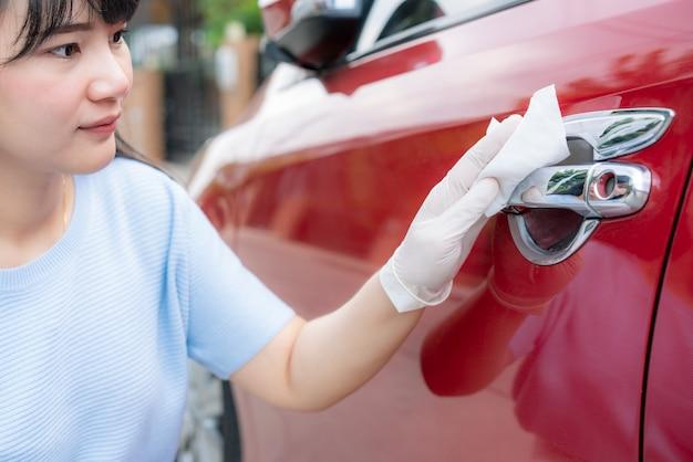 Azjatycka kobieta dezynfekująca klamkę czerwonego samochodu dezynfekującymi chusteczkami jednorazowymi z pudełka. zapobiegaj wirusom i bakteriom, zapobiegaj covid19, wirusowi korony, alkoholowi dezynfekującemu. koncepcja higieny w domu.