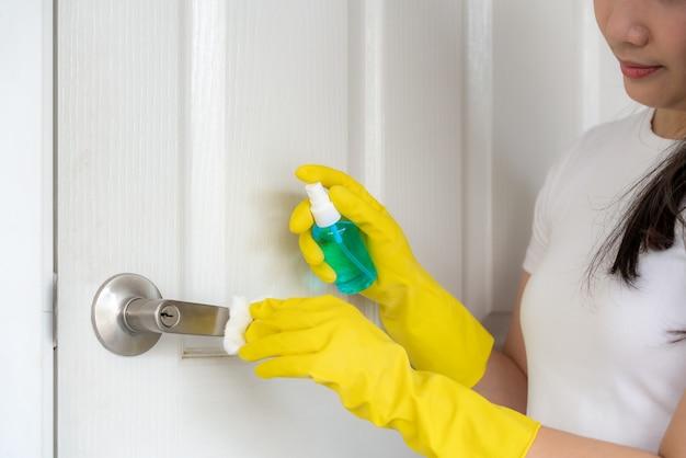 Azjatycka kobieta dezynfekuje klamki drzwi spryskując niebieski środek dezynfekujący z butelki. zapobiegaj wirusom i bakteriom, zapobiegaj covid19, koronawirusowi, alkoholowemu odkażalnikowi. koncepcja higieny w domu.