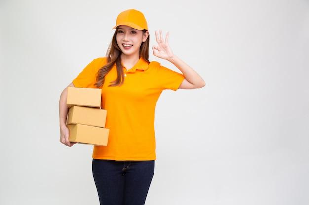 Azjatycka kobieta dostawy gospodarstwa paczkę w pomarańczowym mundurze na białym tle