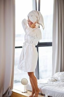 Azjatycka kobieta dotyka głowy w ręcznik, stoi po prysznicu, ciesząc się czasem dla siebie, koncepcja piękna