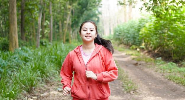 Azjatycka kobieta działa w lesie na sobie kurtkę
