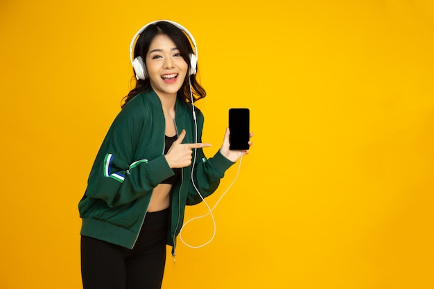Azjatycka kobieta fitness słuchająca muzyki ze słuchawkami na smartfonie i wskazująca palcem na telefon na białym tle na żółtym tle