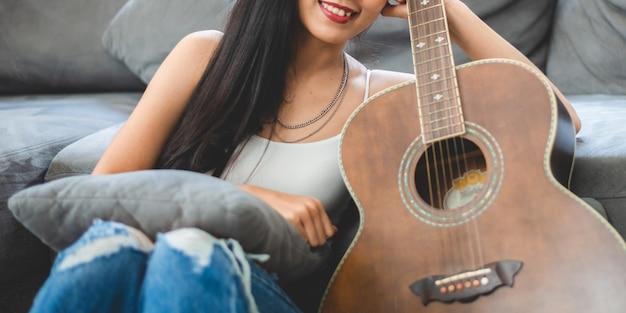 Azjatycka kobieta grająca muzykę na gitarze w domu, młoda kobieta gitarzysta muzyk, styl życia z instrumentem akustycznym, siedzącym, by grać i śpiewać piosenkę, wydając dźwięk w hobby w pokoju domowym