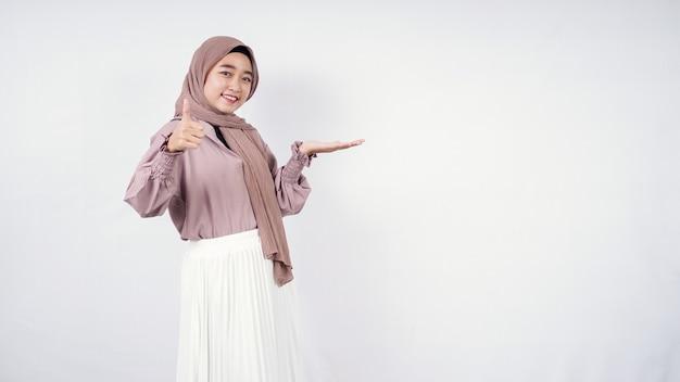 Azjatycka kobieta hidżab wskazująca puste po lewej stronie i w porządku na białym tle