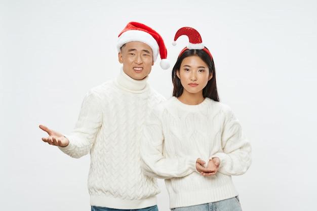 Azjatycka kobieta i mężczyzna pozuje wraz z santa kapeluszami