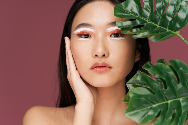 Azjatycka kobieta jasny makijaż zielone liście nagie ramiona czysta skóra
