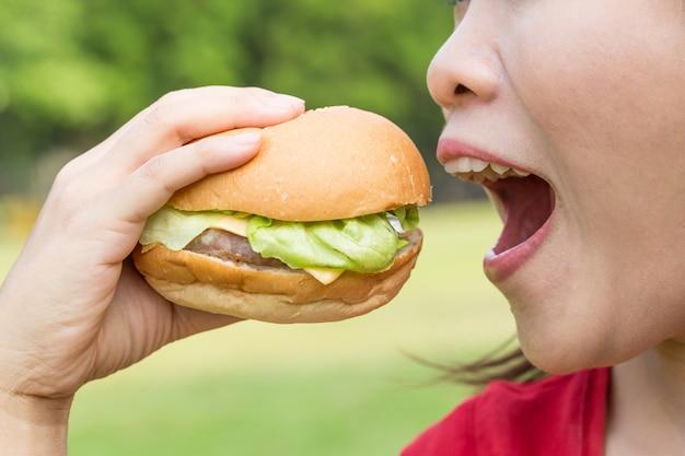 Azjatycka kobieta je hamburger bardzo głodnego.