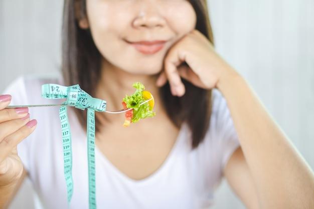 Azjatycka kobieta je zdrowej karmowej sałatki