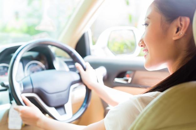 Azjatycka kobieta jedzie nowego samochód