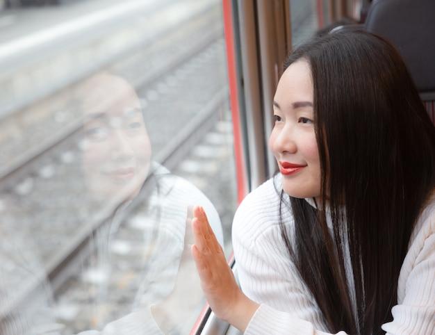 Azjatycka kobieta jest przyglądającym widokiem naturalnym z okno w pociągu