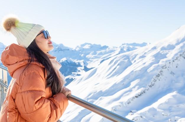 Azjatycka kobieta jest szczęśliwa i patrzejąca śnieżnego widok górskiego.