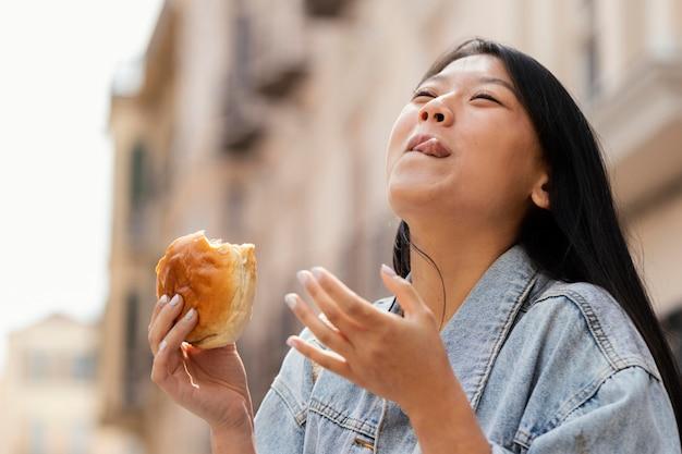Azjatycka kobieta jest szczęśliwa po zakupie ulicznego jedzenia