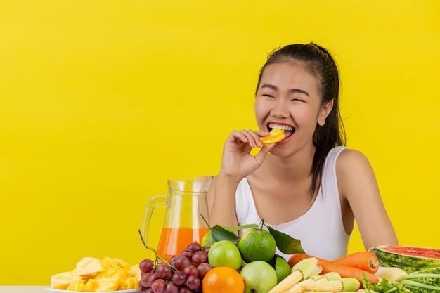 Azjatycka kobieta jest ubranym białego podkoszulek bez rękawów. jedzenie ananasa a stół jest pełen różnego rodzaju owoców.