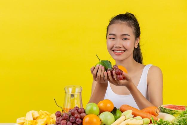 Azjatycka kobieta jest ubranym białego podkoszulek bez rękawów. obie ręce trzymały owoce, a stół jest pełen różnych owoców.