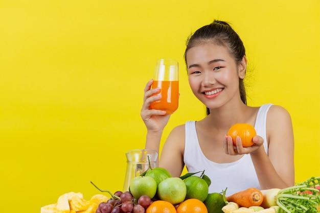 Azjatycka kobieta jest ubranym białego podkoszulek bez rękawów. trzymanie szklanki soku pomarańczowego prawą ręką lewa ręka trzymała pomarańczę i na stole było wiele owoców.