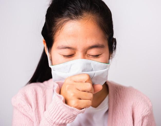 Azjatycka kobieta jest ubranym chirurgicznie ochrony twarzy maski sukienną higienę przeciw koronawirusowi i jej kichnięcie ręki zakończenia usta