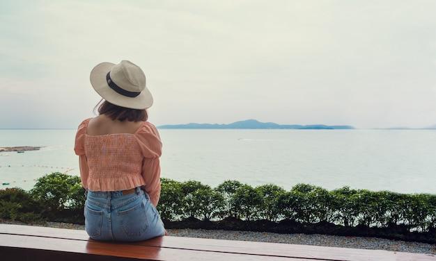 Azjatycka kobieta jest ubranym kapelusz i przypadkową odzież, siedzi z powrotem i patrzeje widok na morze i górę