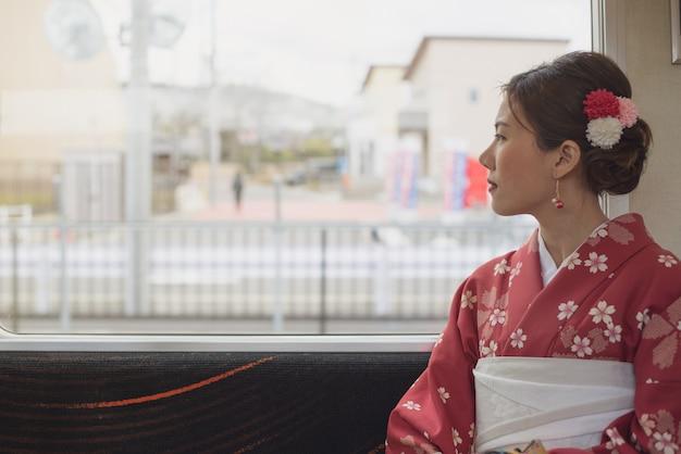 Azjatycka kobieta jest ubranym kimono podróżuje japan klasyka pociągiem siedzi blisko okno
