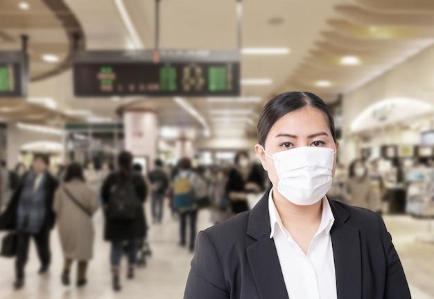 Azjatycka kobieta jest ubranym maskę chirurgiczną, aby zapobiec chorobie grypowej wirus korony z zamazanym wizerunkiem zatłoczonym