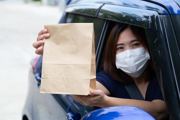 Azjatycka kobieta jest ubranym maskę i trzyma papierową torbę fast food przez nadokiennego samochodu. przejedź przez koncepcję usług gastronomicznych