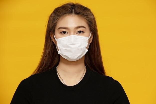 Azjatycka kobieta jest ubranym maskę ochronną lub chirurgiczną maskę dla chronionego wirusa i zanieczyszczenia powietrza