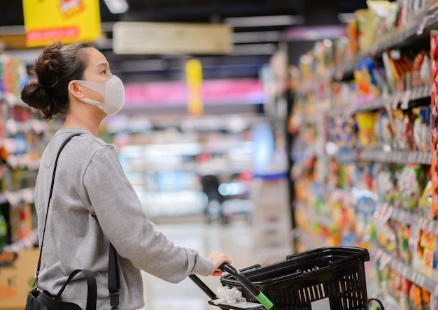 Azjatycka kobieta jest ubranym maskę w supermarkecie