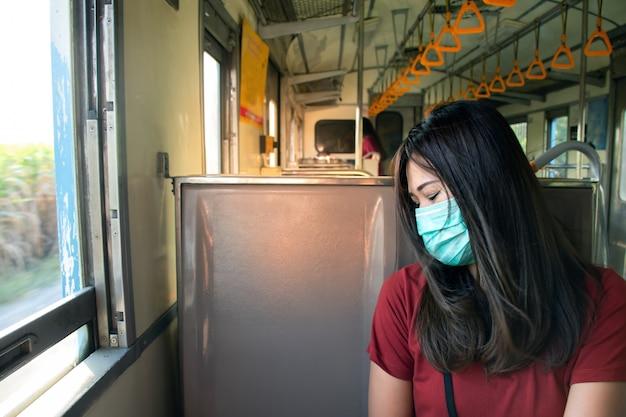 Azjatycka kobieta jest ubranym maskę z powodu zanieczyszczenia powietrza w pociągu