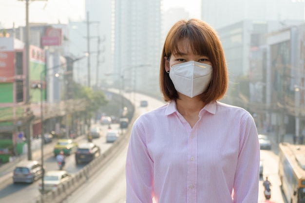 Azjatycka kobieta jest ubranym n95 oddechowej ochrony maskę przeciw zanieczyszczeniu powietrza przy drogą i ruchem drogowym w bangkok