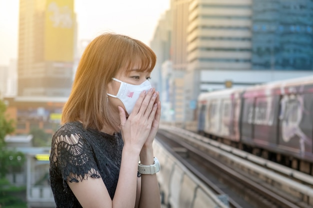Azjatycka kobieta jest ubranym n95 oddechowej ochrony maskę przeciw zanieczyszczeniu powietrza przy niebo dworcem