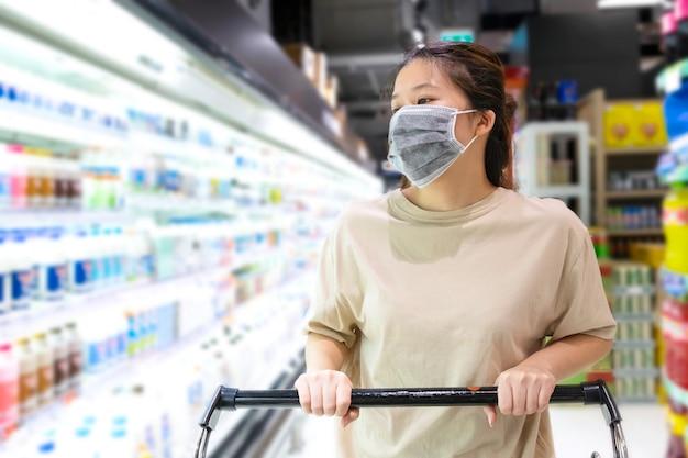 Azjatycka kobieta jest ubranym ochronną twarzy maskę z wózek na zakupy przy supermarketem