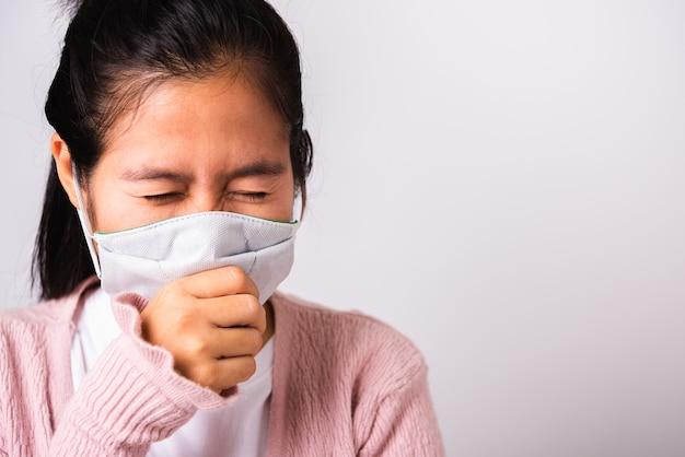 Azjatycka kobieta jest ubranym ochrony twarzy maski higienę przeciw coronavirusowi i kicha ręki zakończenia usta