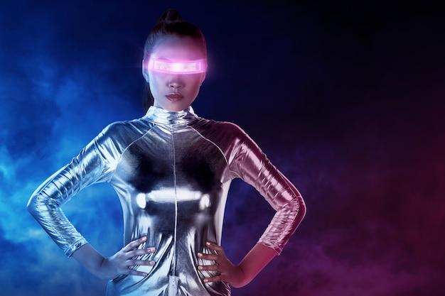 Azjatycka kobieta jest ubranym srebnego lateksowego kostium