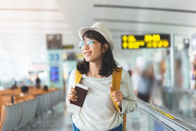 Azjatycka kobieta jest ubranym szkła, kapelusz z żółtym plecakiem trzyma latającego bilet, paszport przy sala lotnisko.