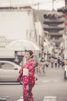 Azjatycka kobieta jest ubranym tradycyjnego japońskiego kimono chodzi w starym miasteczku kyoto