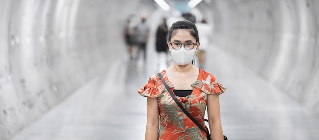 Azjatycka kobieta jest ubranym twarzy maskę ochrania koronawirusa fleksję